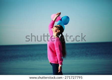 Beach woman laughing having fun in vacation holidays. Beautiful hipster girl dressed in bright youth clothes walking in the beach, holding colored balloons. Photo toned style Instagram filters. - stock photo