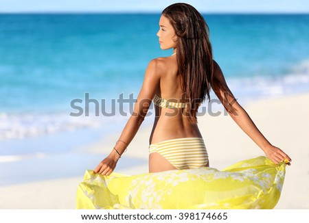 Beach woman relaxing in yellow bikini and cover-up pareo beachwear enjoying sunset. Beautiful Asian girl model from the back for suntan skincare or weight loss cellulite sexy body concept. - stock photo