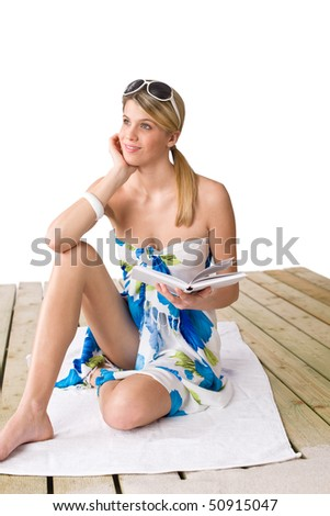 Beach - woman sitting on wooden deck with book, sunbathing, wearing pareo