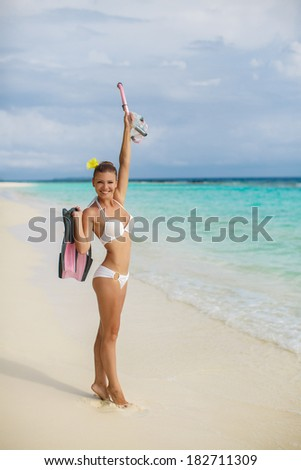 Beach woman snorkeling walking happy enjoying sun and holidays travel in sunny sunshine wearing bikini holding snorkel, fins and mask. Beautiful excited mixed race Asian Caucasian bikini girl. - stock photo
