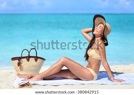 Beach woman sun tanning on summer tropical vacation wearing a cute retro stripes bikini and hat outfit with straw bag and towel.