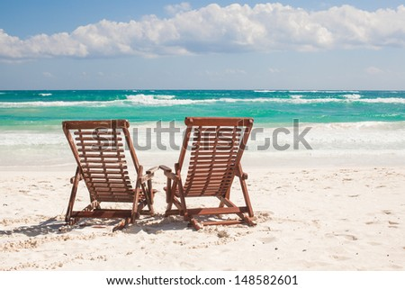 Beach wooden chairs for vacations and relax on tropical beach in Tulum, Mexico