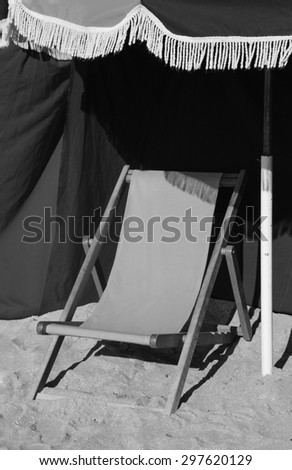 Beach wooden chaise lounge and umbrella with fringe. Trouville-sur-Mer (Normandy, France). Selected focus on the fringe. Aged photo. Black and white. - stock photo