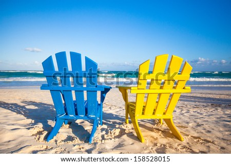 Beach wooden colorful chairs for vacations and summer getaways in Tulum, Mexico - stock photo