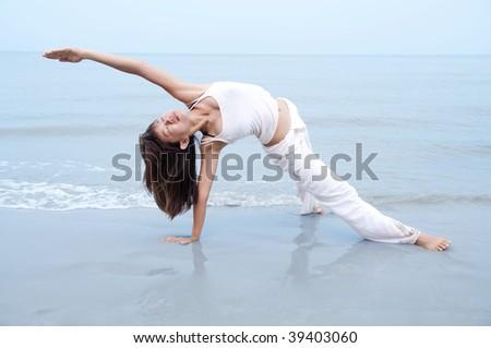 Beach Yoga. Woman practicing Yoga(Gate Pose) on the beach. - stock photo
