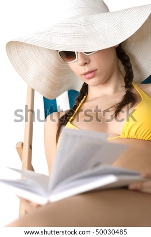 Beach - Young woman in bikini relax with book sunbathing on deckchair - stock photo