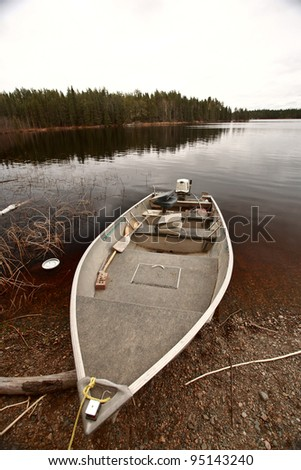 beached motor boat on Northern Manitoba lake - stock photo