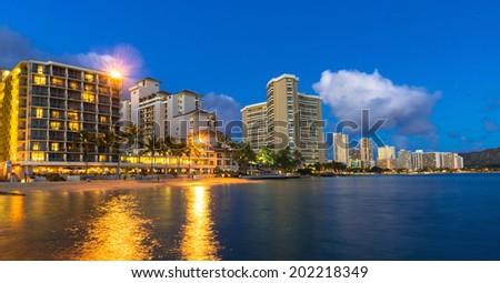 Beachfront hotels on Waikiki beach in Hawaii against a blue night sky - stock photo