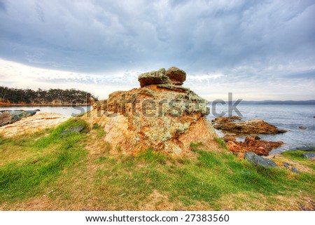 Beachside boulder against blue sky and green grass - stock photo
