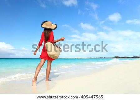 Beachwear woman tourist with straw sun hat and beach bag walking on tropical summer vacation wearing sunhat and red tunic dress cover-up relaxing on travel holidays from behind. - stock photo