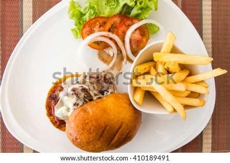 Beacon cheese burger with fries on a white plate with salad - stock photo