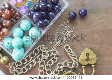 Beads and tools on wooden floor flat lay - stock photo