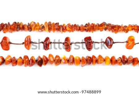 Beads of amber laid in a row isolated on white background - stock photo