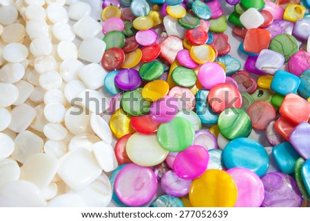 Beads of round colorful stones lie on the counter of souvenir shop on the beach in Dominican republic