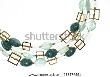 Beads with green gems on a white background - stock photo