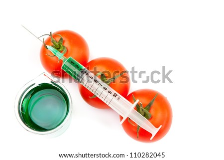 Beaker next to syringe on tomatoes against a white background - stock photo