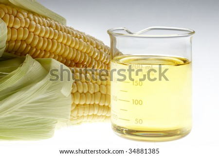 Beaker of of ethanol and ears of corn shot on lightbox - stock photo