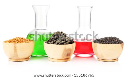 Beakers with bio fuel from rape seeds, oil cakes, isolated on white - stock photo
