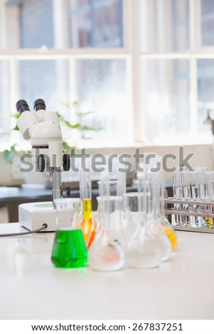 Beakers with chemical fluid and microscope in laboratory