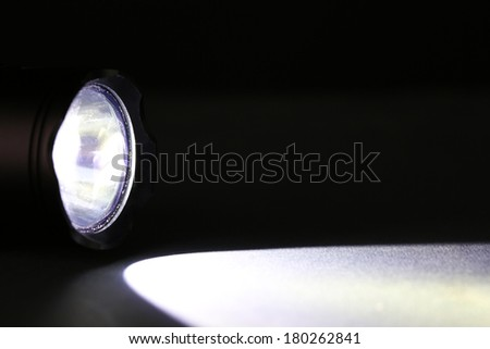 Beam from flashlight closeup on dark background - stock photo