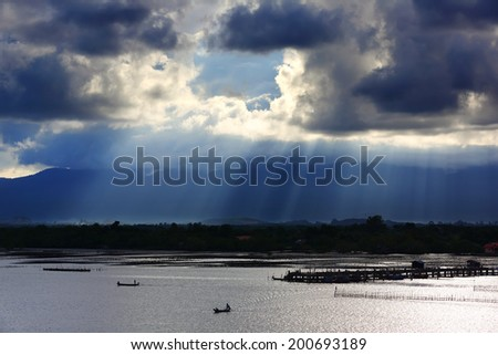 Beam light and Aquaculture with fishing boats sailing at morning light,Thailand - stock photo