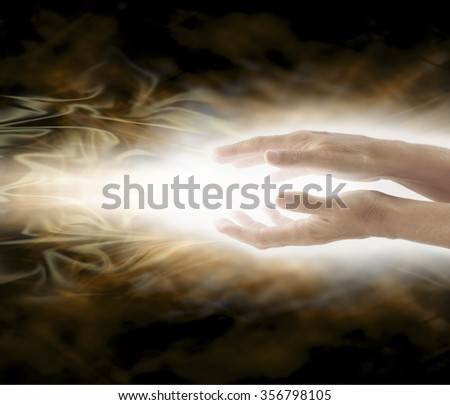 Beaming Reiki Healing Energy - Female with hands held parallel  sending healing energy on a swirling misty ethereal golden brown background and plenty of copy space - stock photo