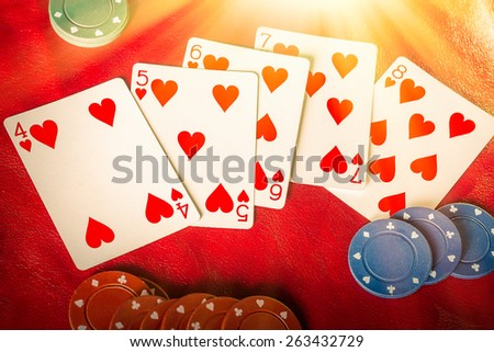 Beams of heavenly light illuminate a winning hand, straight flush of hearts  - stock photo