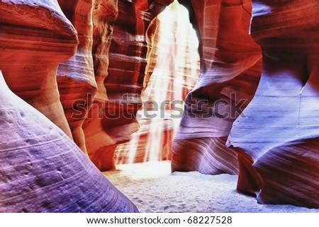 Beams of sun light descending to canyon floor in Antelope Canyon through the cracks above - stock photo