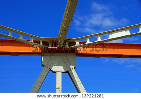 Beams of the bridge on a background of the blue sky - stock photo