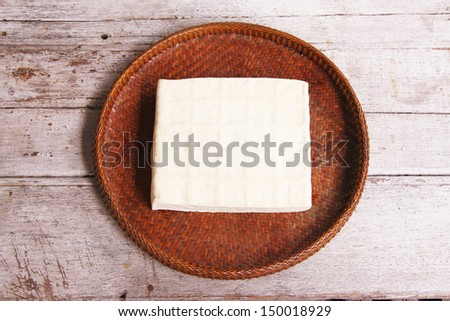 bean curd,tofu in the threshing basket on wooden table - stock photo