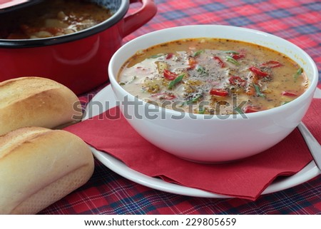 Bean soup in a white bowl on a white plate.