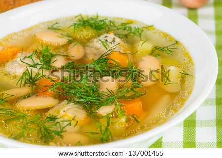 Bean soup with meatballs, vegetables and dill - stock photo