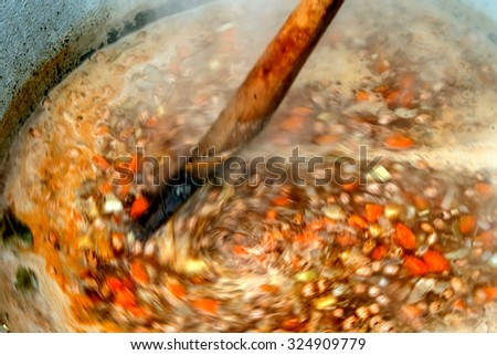 Bean soup with vegetables, prepared traditionally in a large bowl and mixed with a wooden spoon. - stock photo
