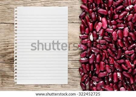 Beans and paper for recipe on wooden background - stock photo