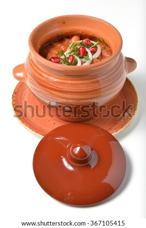 beans baked in a ceramic pot decorated with onion rings and pomegranate seeds - stock photo