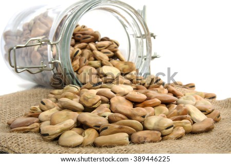 Beans in glass jar and on jute cloth isolated over white - stock photo