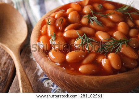 beans in tomato sauce in a wooden bowl closeup. horizontal - stock photo