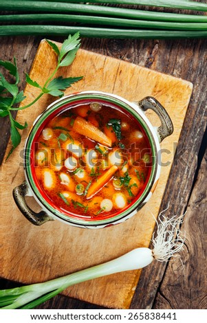 Beans soup on a rustic wooden board with spring onion. - stock photo