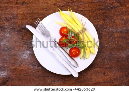 Beans, tomatoes and fresh herbs on a plate Healthy food background. - stock photo