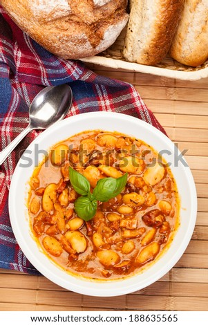 Beans with tomato sauce, bacon and sausage on a plate
