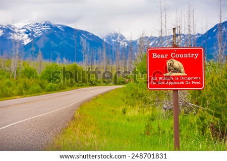 Bear Country Warning Sign. All Wildlife is Dangerous. Do Not Approach or Feed Red Countryside Sign. Montana, United States. - stock photo