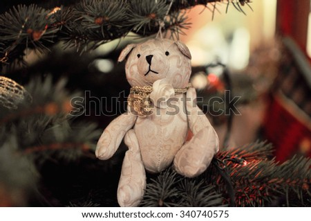 Bear fabric sitting on the branch of Christmas tree