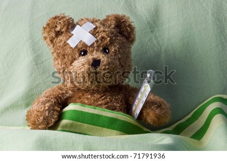 bear in bed with thermometer and plaster - stock photo