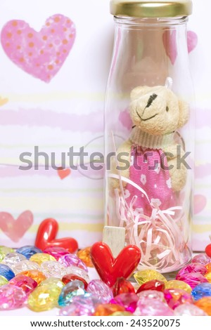 Bear in glass bottles with glass hearts of many colors,decoration.