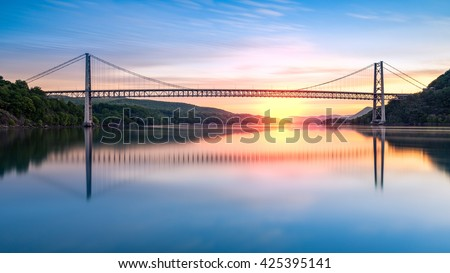 Bear Mountain Bridge at sunrise (long exposure). Bear Mountain Bridge is a toll suspension bridge in New York State, carrying U.S. Highways 202 and 6 across the Hudson River - stock photo