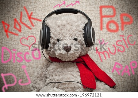 Bear music fan listens to music on headphones  - stock photo