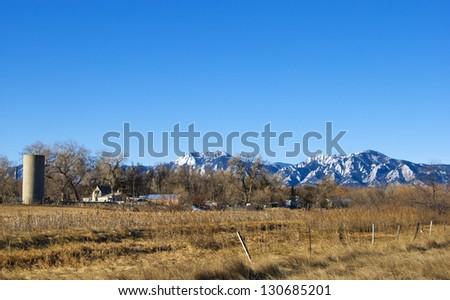 Bear Peak, Green Peak and the Flatirons tower above a peaceful farm on the Colorado prairie near Boulder. - stock photo