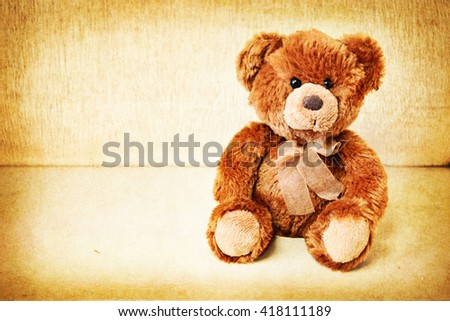 Bear seated against a old wooden wall. Vintage background