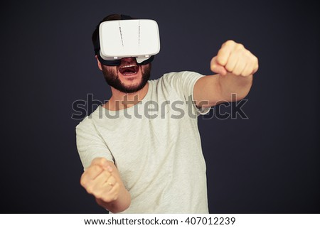 Beard man driving in virtual reality wearing hi-tech VR headset, on black background - stock photo