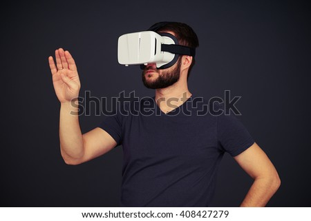 Beard man touch something with right hand and looks to the right side in virtual reality, on black background - stock photo